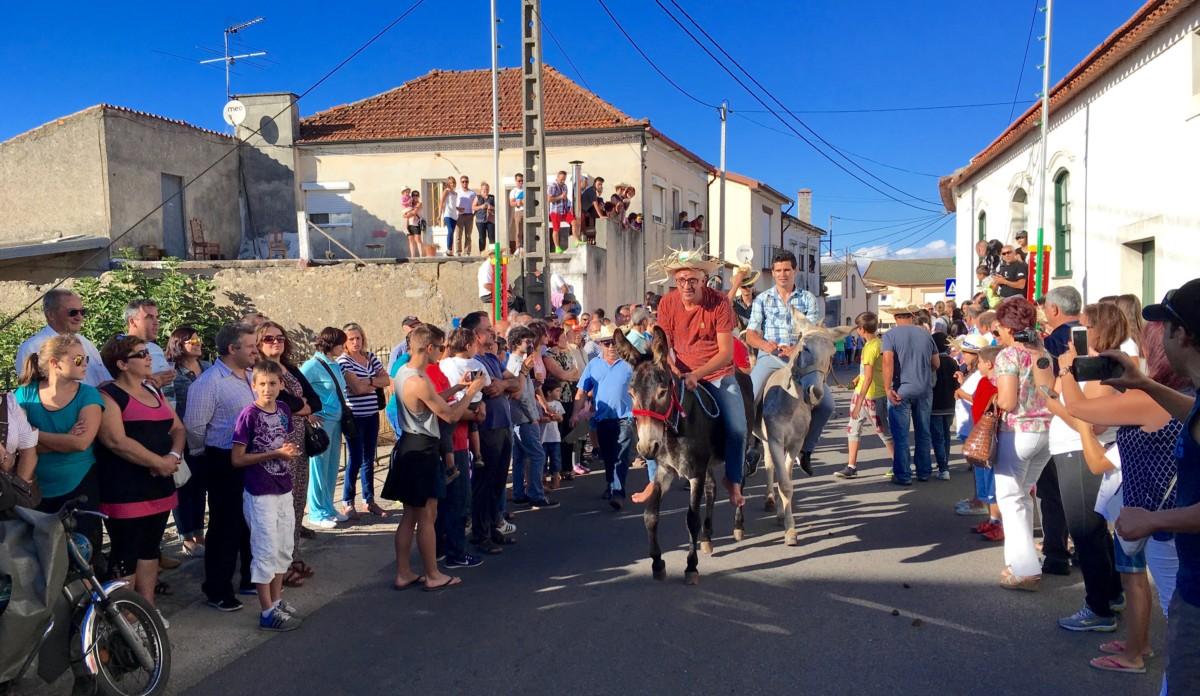 De deelnemers aan de ezelrace rijden op en neer door de hoofdstraat