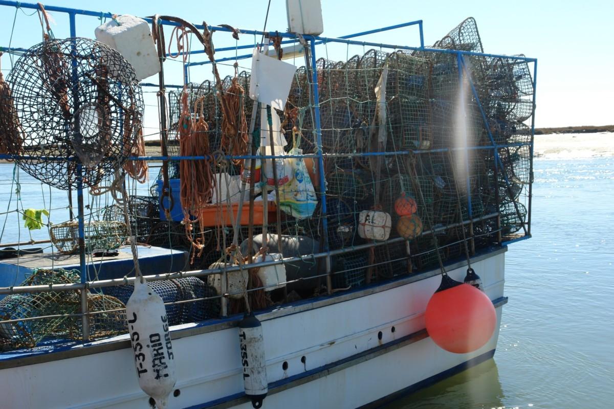 Vissersboot met een stapel vangkorven van metaal om octopus mee te vangen.
