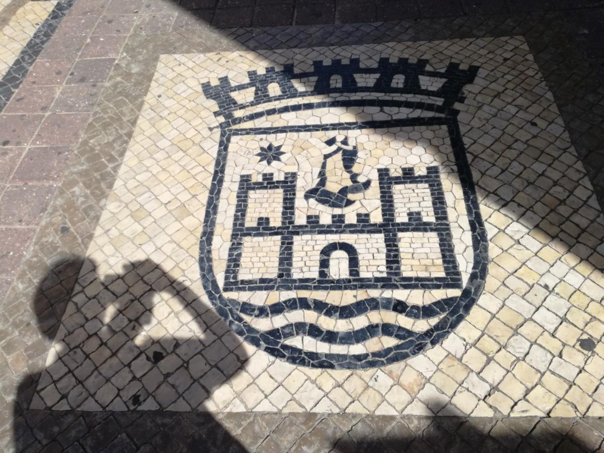 Het stadswapen van Faro uitgevoerd in mozaïek: een kasteel met twee torens met water ervoor.