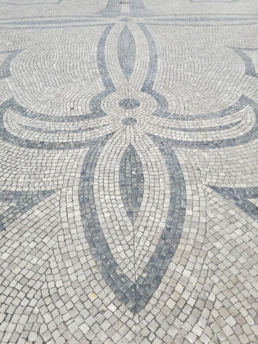 Sierlijke lijnen mozaïek van zwarte en grijze keitjes in Tavira.