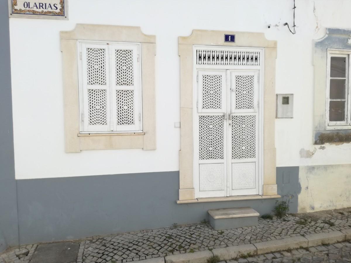 Een witte deur en een raam met panelen met fijn traliewerk waardoor je niet naar binnen kunt kijken. Andersom kan dat wel.