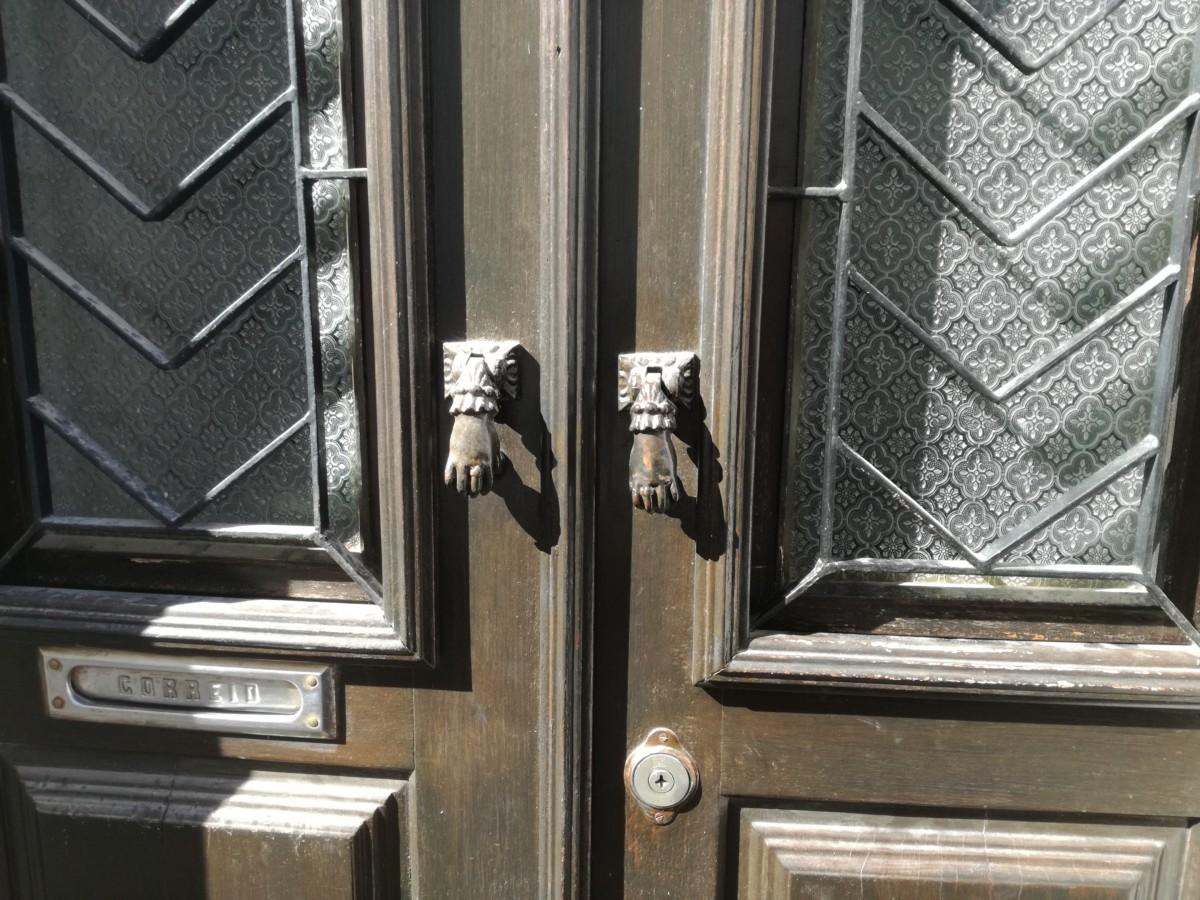 Een bruine voordeur met twee kleiner handjes met kanten manchetjes.