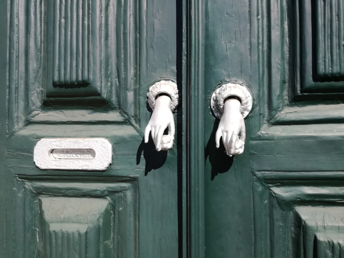 Groene voordeuren met twee rechterhanden die een appeltje vasthouden.