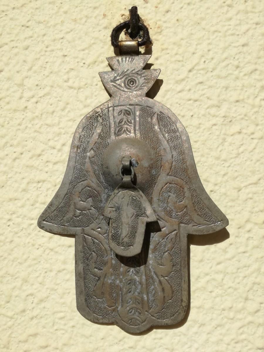 Een koperen handje van Fatima, een islamitisch symbool van een gestileerde hand met vijf vingers.