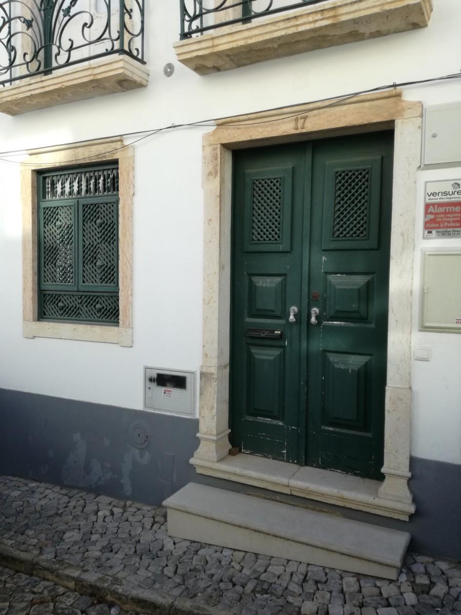 Groene deur met twee traliewerkpaneeltjes en een raam dat geheel uit fijn traliewerk bestaat.