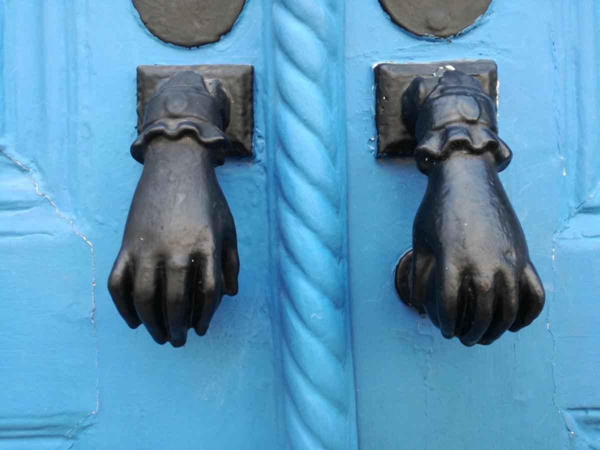 Een lichtblauwe deur met twee zwarte handjes met een ring aan de middelvinger en een kanten manchet.