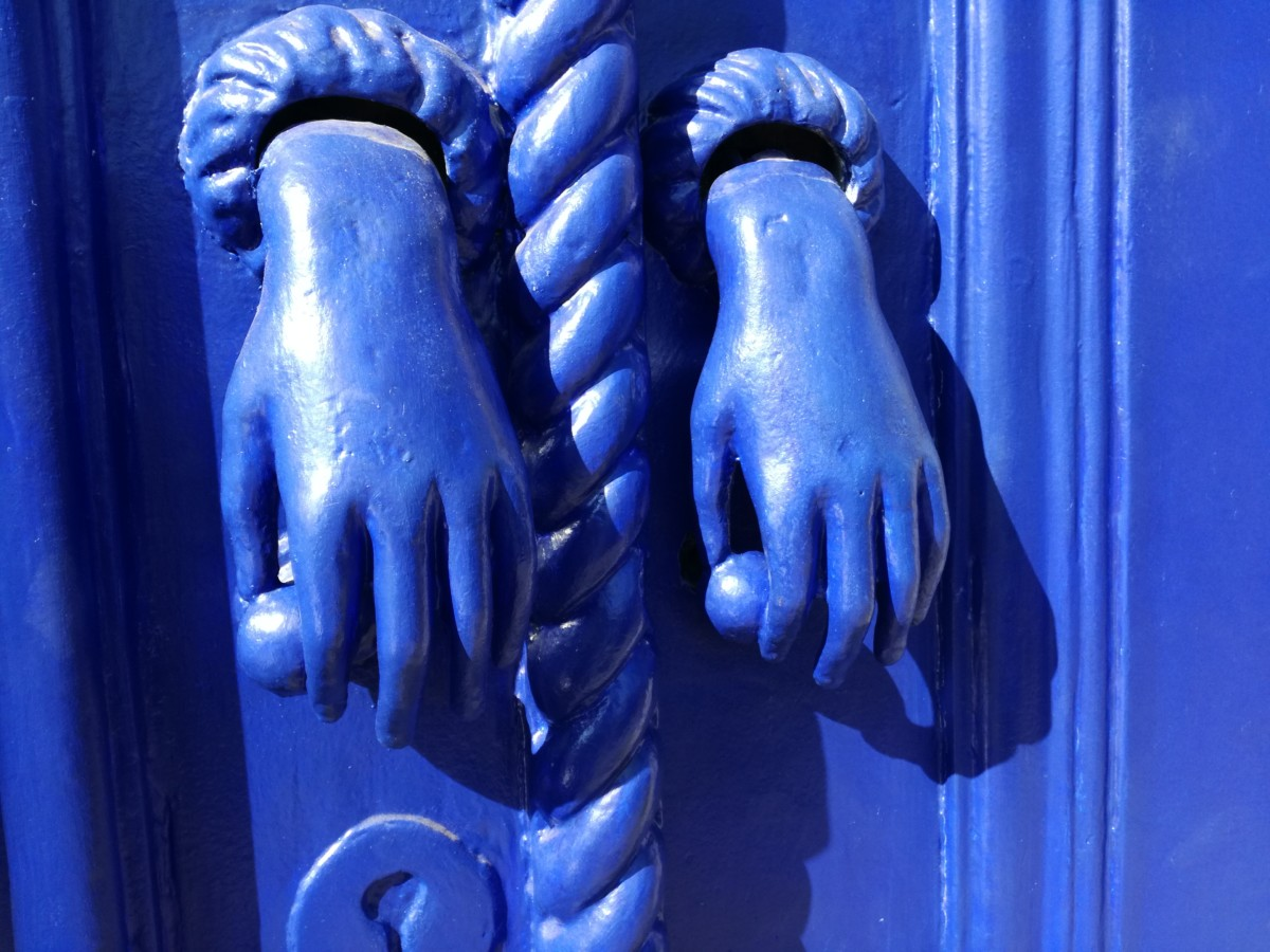 Een azuurblauwe deur met twee linkerhanden in dezelfde kleur met een balletje tussen duim en wijsvinger.