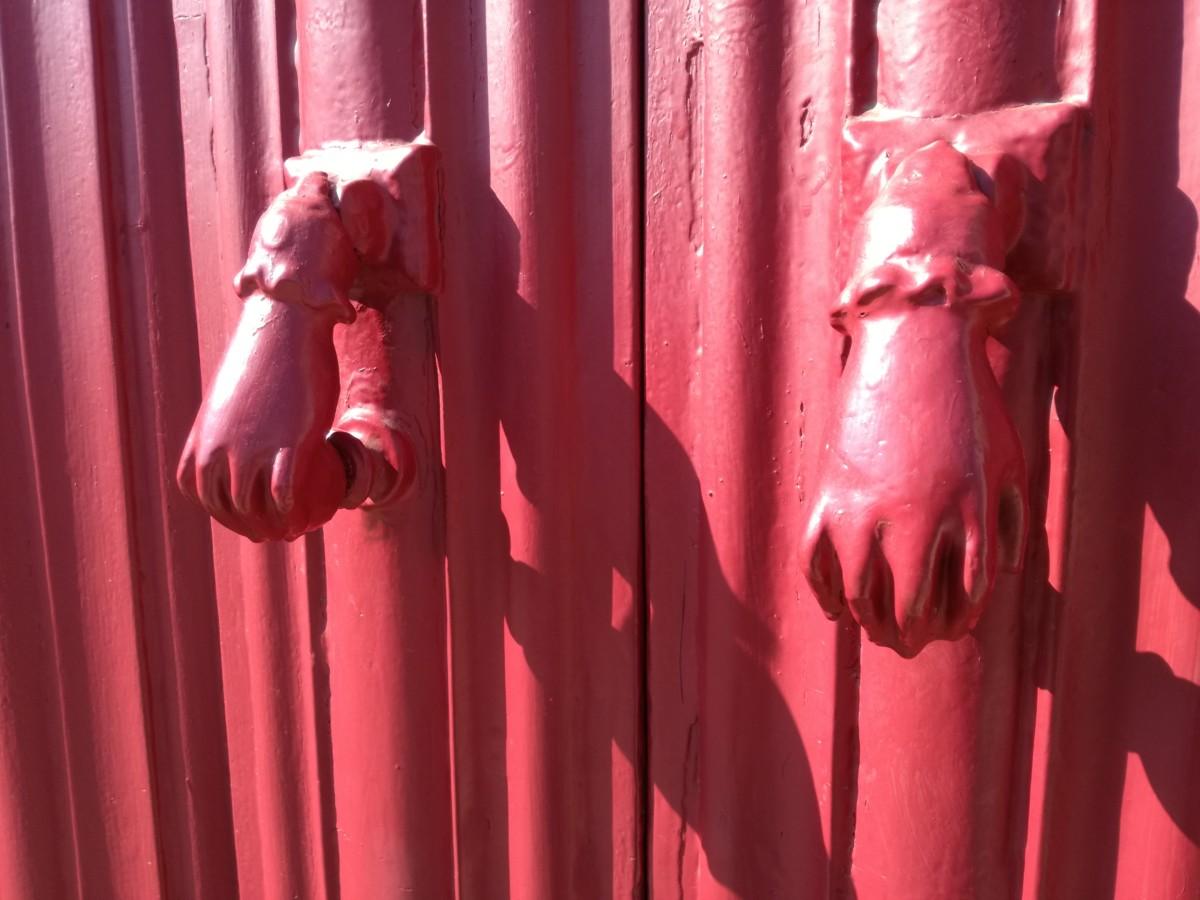 Een roze deur met twee handjes in dezelfde kleur die wel op kinderknuistjes lijken.