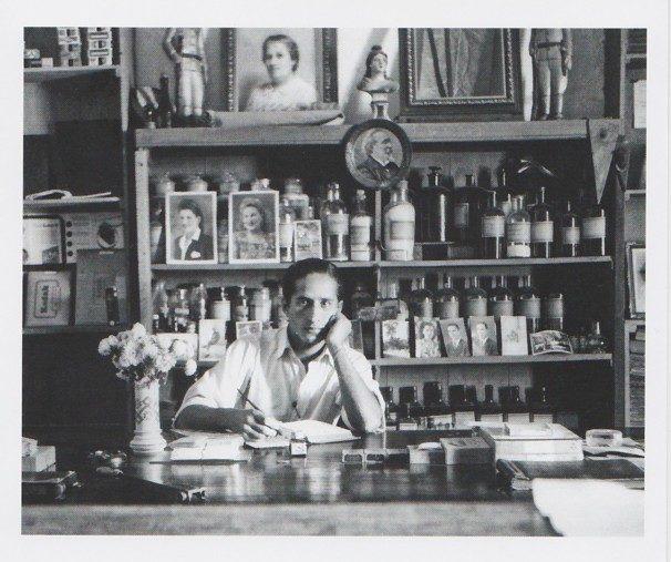 Zwart-wit foto van een fotograaf in zijn fotostudio met achter hem een kast vol flessen ontwikkelaar e.d.