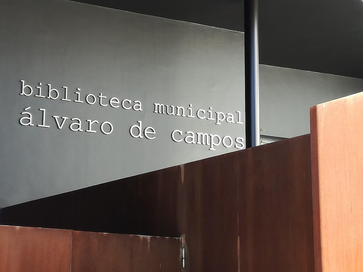 De ingang van de bibliotheek in Tavira. De toegang is van roestkleurig staal en op de zwarte muur erachter staat de naam: biblioteca municipal álvaro de campos.