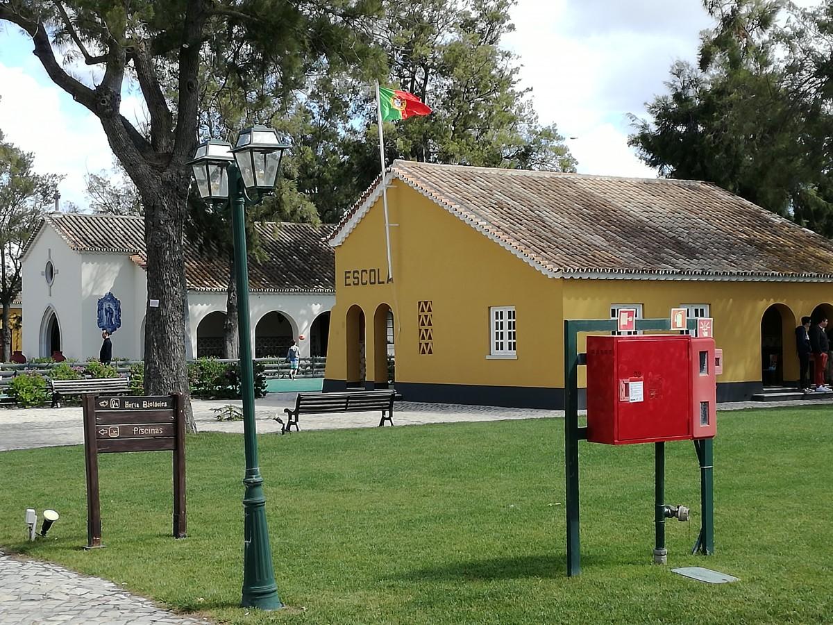 Klein geel schoolgebouwtje en klein wit kerkje in het dorp van de tonijnvissers. Nu deel van een groot horel.