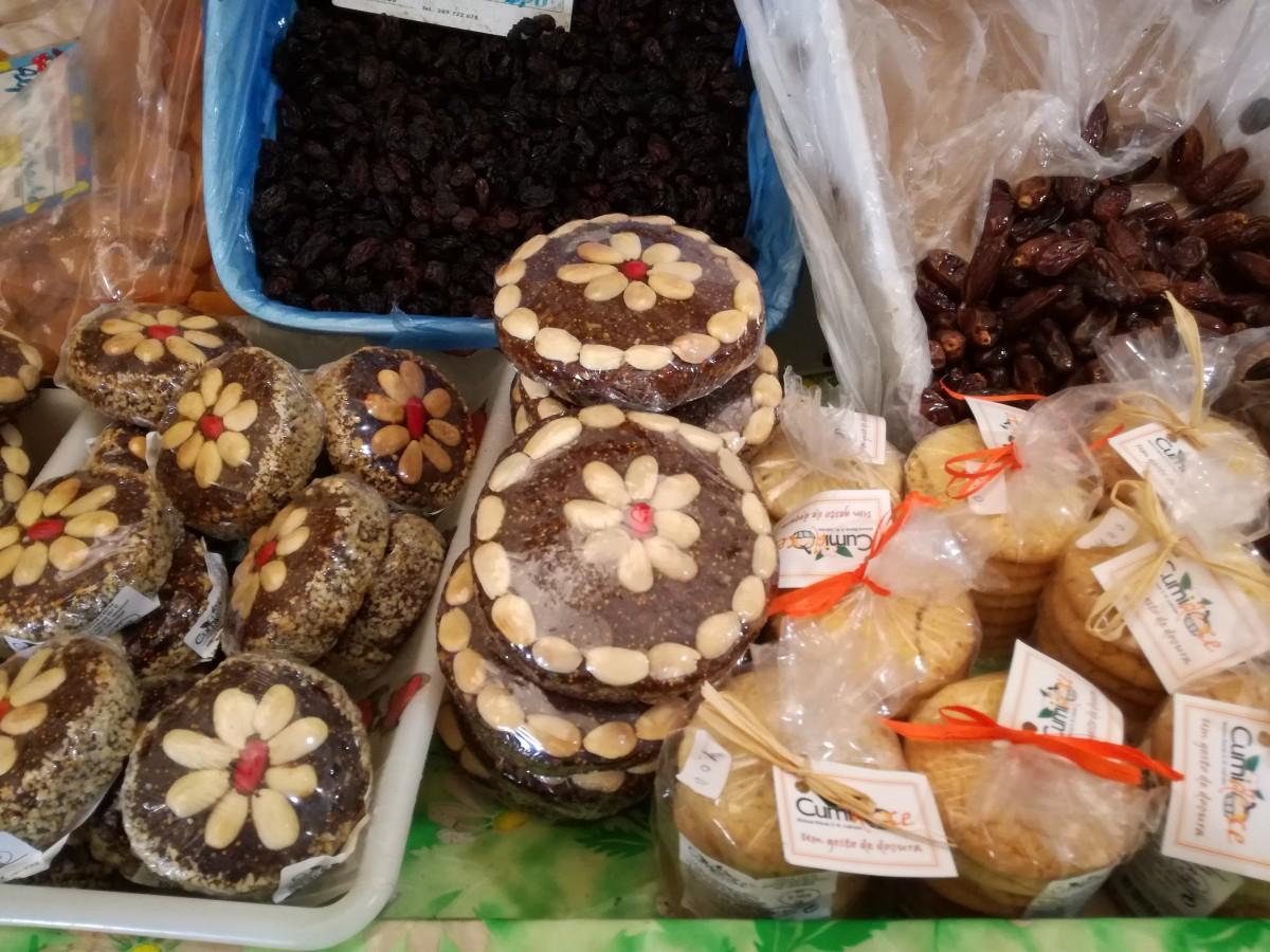 Platte, ronde vijgenkoeken, mooi versierd met amandelen in bloemvorm op de markt. Ernaast liggen rozijnen, dadels en amandelkoeken.