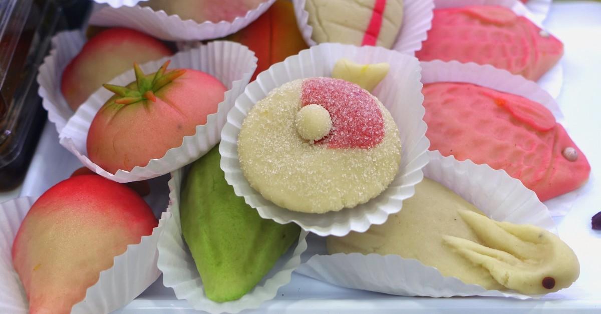 Kleurige marsepeinen gebakjes in de vorm van vruchten en visjes.