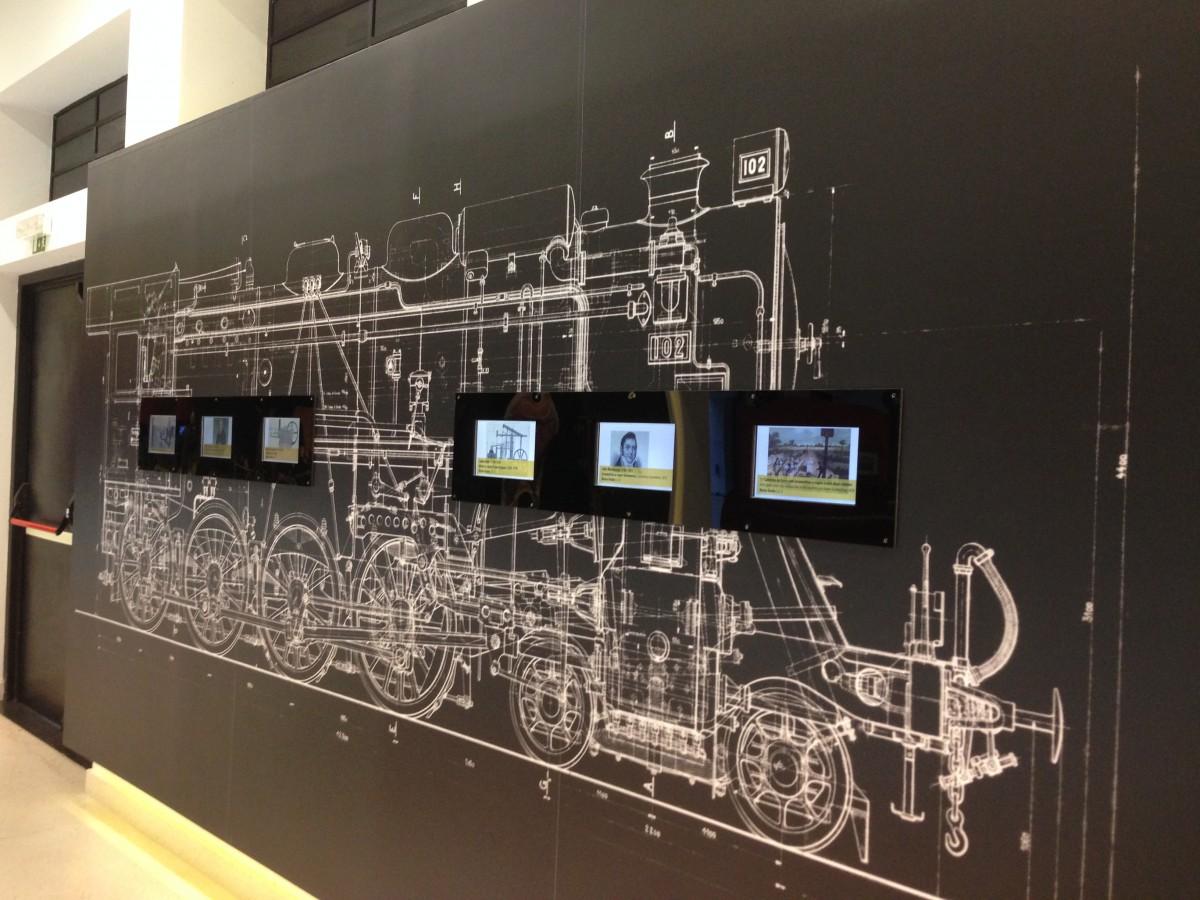 wand in het treinmuseum met digitale schermen