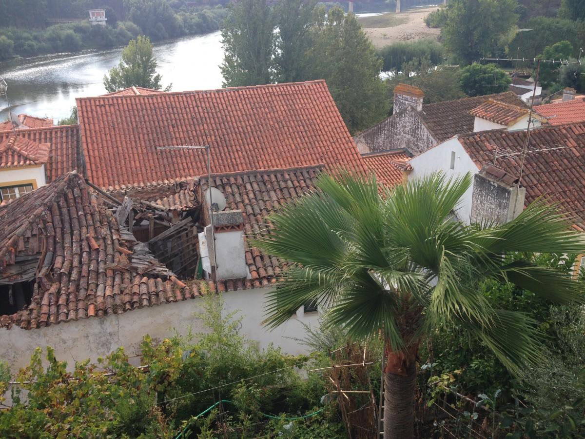 Zicht op de rivier en daken van huizen vanaf een terras.