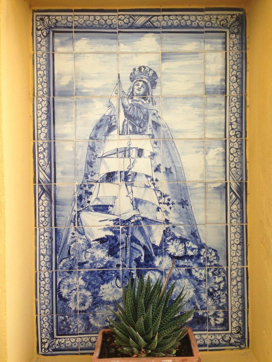 Tegeltableau in de hal van het museum, met voorstelling van een zeilschip met een Mariabeeld.