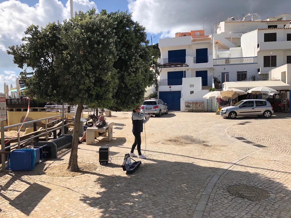 Violiste op het plein, onder de boom
