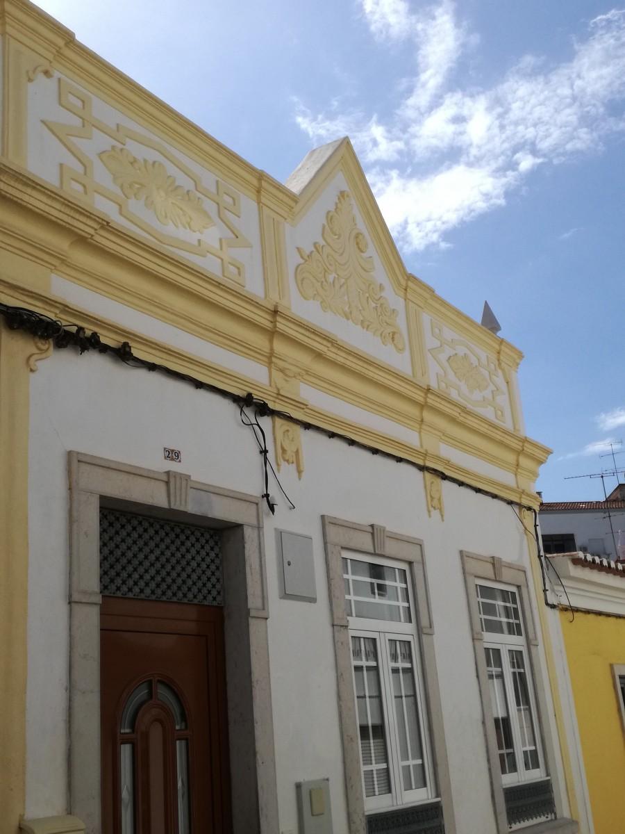 Een wit huisje met een hoge daklijst met bladpatronen in stucwerk die geel zijn geschilderd.
