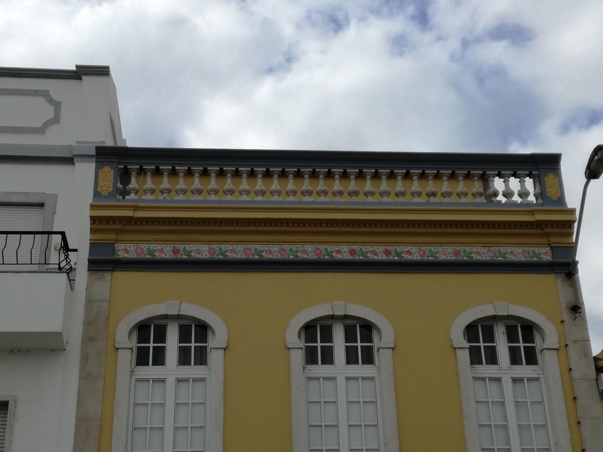 Geel huis met een daklijst met talloze pilaartjes.