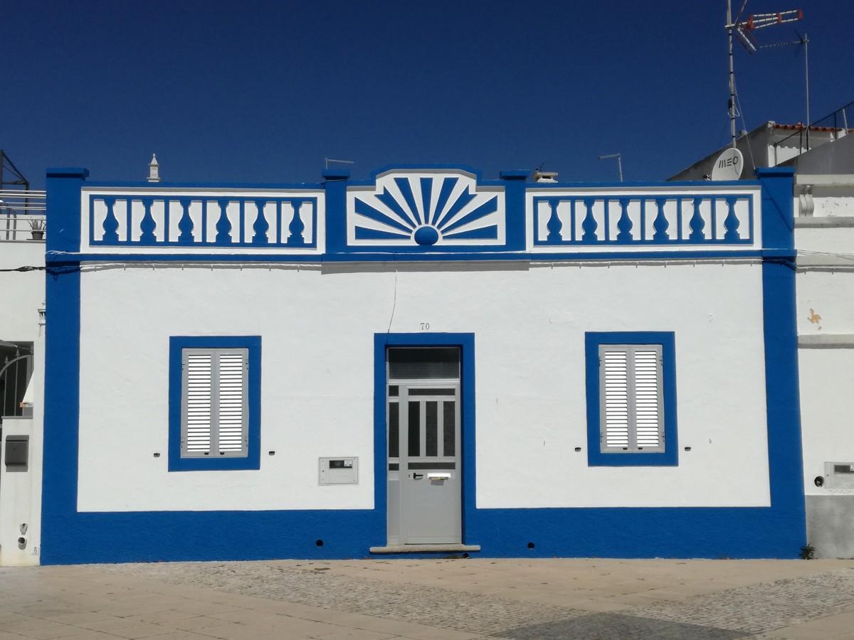 Een wit huisje met deur in het midden en links en rechts van de deur een raam. De gevel is van een azuurblauwe rand voorzien en de daklijst is met die kleur bewerkt.