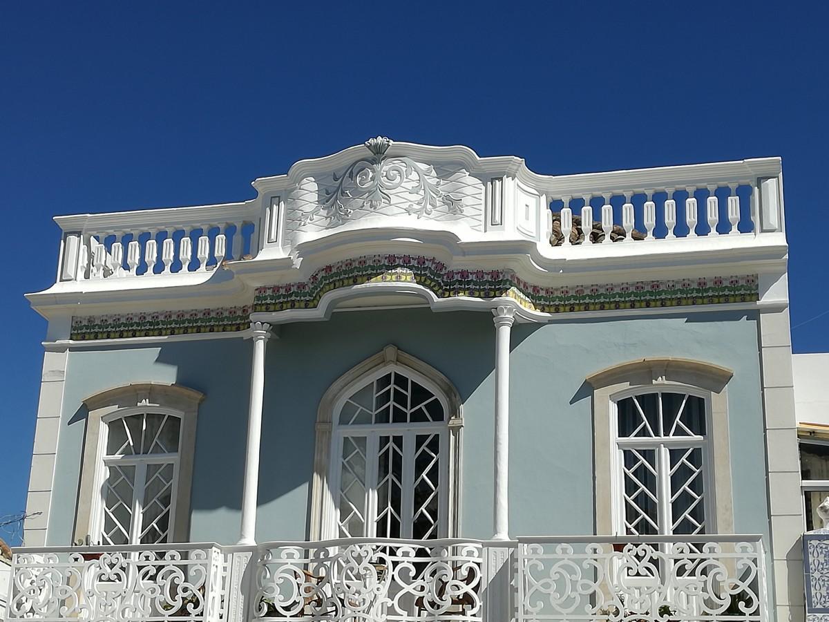 Fraai grijsblauw huis met een witte daklijst met pilaren en bloempatronen. Die herhalen zich in het balkon dat dwars over de gevel loopt.