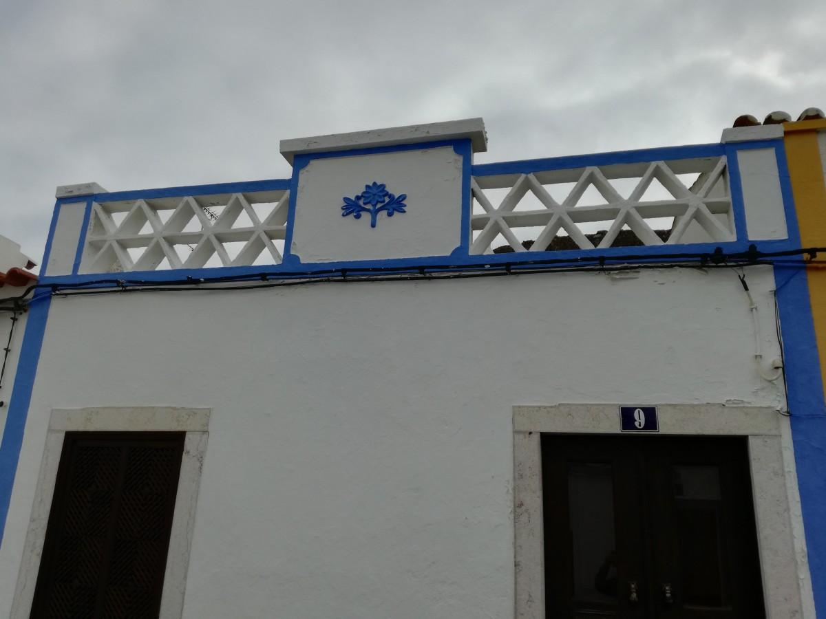 Simpel wit huisje met een opengewerkte daklijst van driehoeken.