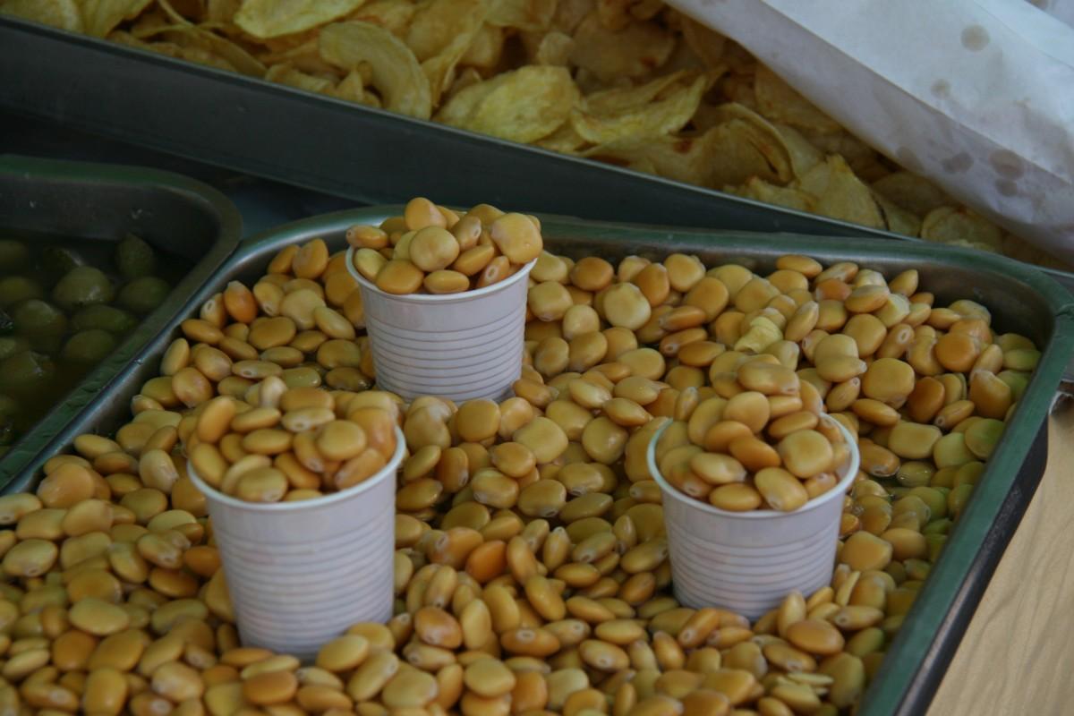 Een bak met tremoços van waaruit met een plastic koffiebekertje hoeveelheden worden opgeschept om te verkopen.