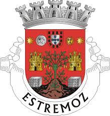 Het wapen van Estremoz met in het midden een plant waaraan tremoços hangen, links en rechts daarvan een kasteeltoren en boven de maan en de zon op een rode achtergrond.
