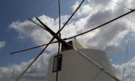 De geheel gerestaureerde windmolen Moinho do Leitão gefotografeerd tegen een blauwe wolkenhemel.