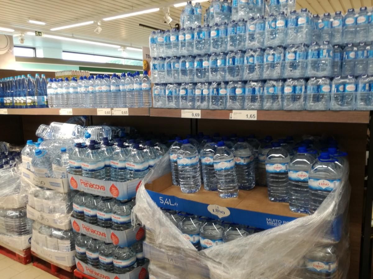 Grootverpakkingen met flessen mineraalwater van verschillende merken in de supermarkt.