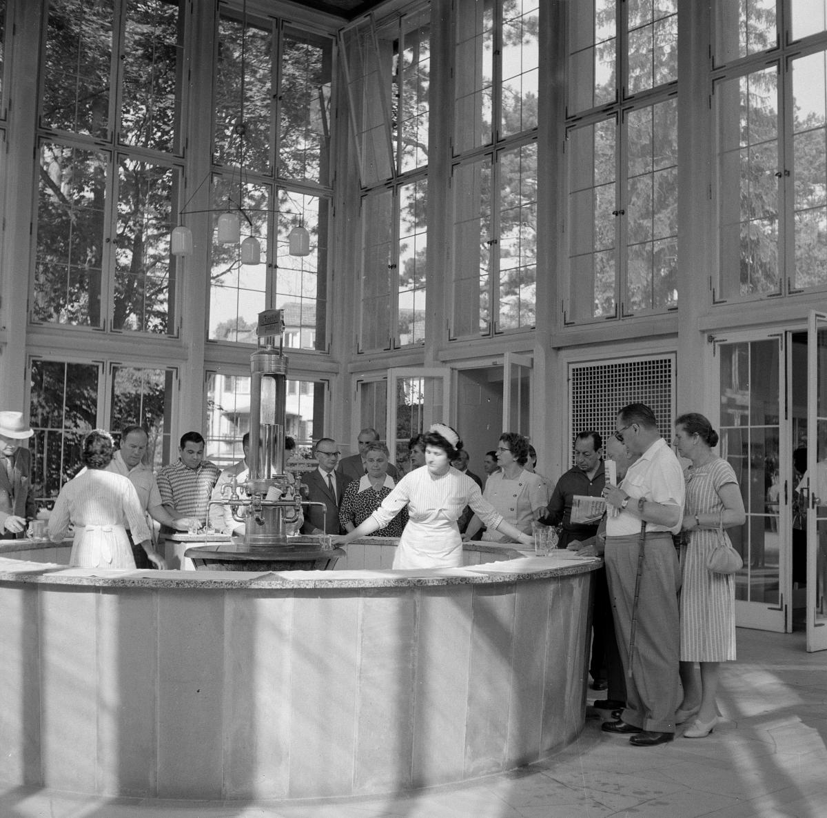 Zwart-witfoto van een kuuroord. In het wit geklede dames vullen glazen met mineraalwater voor de rij wachtenden. De ruimte heeft hoge ramen waardoor buiten veel boomkruinen te zien zijn.