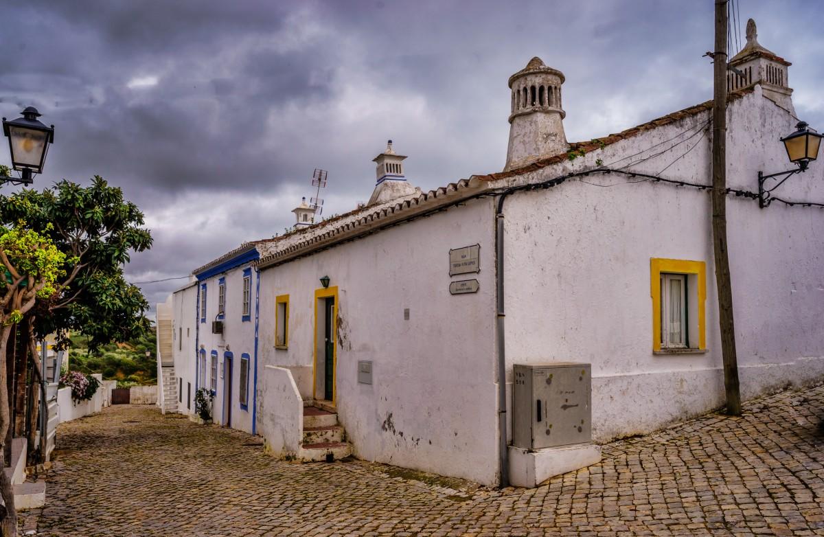 Een straatje in Cacela Velha met karakteristieke eenvoudige huisjes gefotografeerd tegen een donkere lucht.