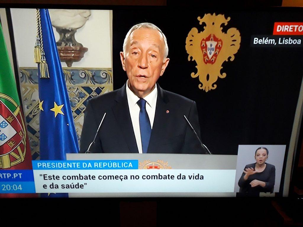 Foto van live TV-toespraak van president Marcelo Rebelo de Sousa met Portugese vlag en wapen, alsmede de EU-vlag op de achtergrond.