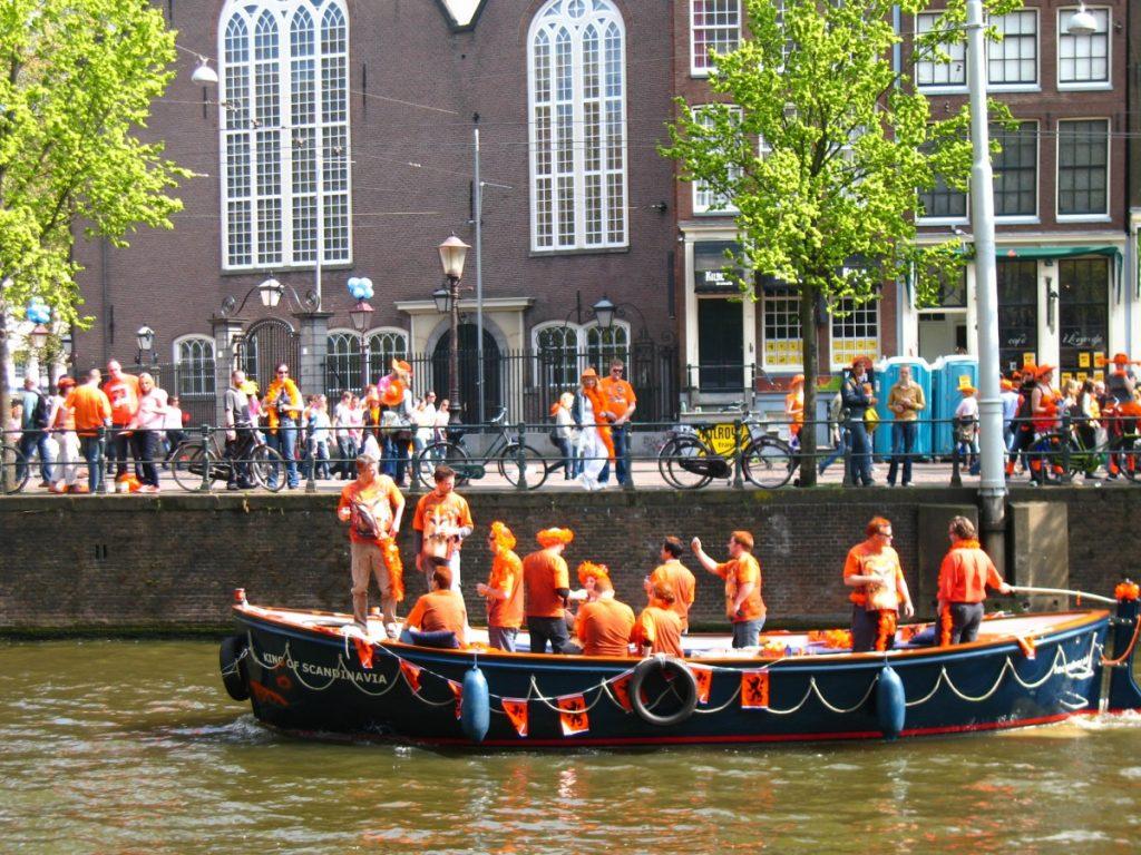 Feestvierders in Amsterdam gekleed in oranje met veel oranje uitingen