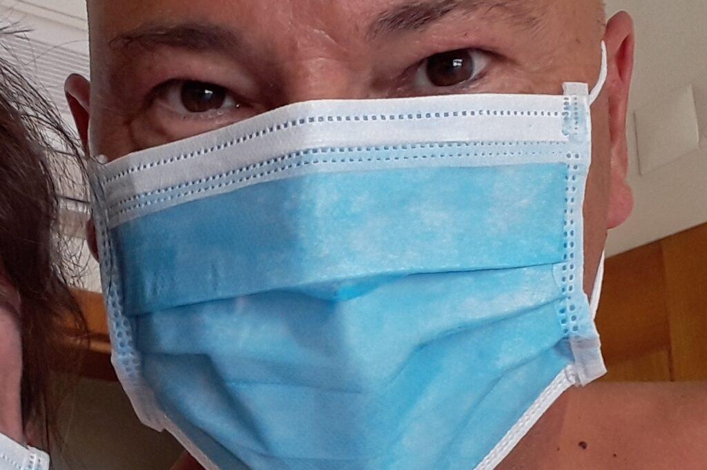 Schrijver Cees Groenewegen met gezichtsmaskertje ofwel mondkapje.