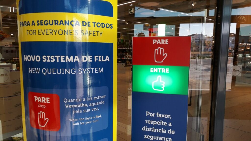 Stoplicht bij de ingang van een supermarkt met uitleg in Portugees en Engels.