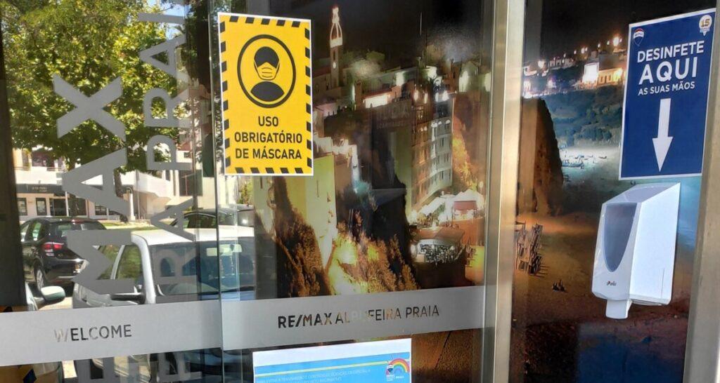 Handgel dispenser en maskertjes waarschuwingsbord bij de ingang van een REMAX winkel in Albufeira
