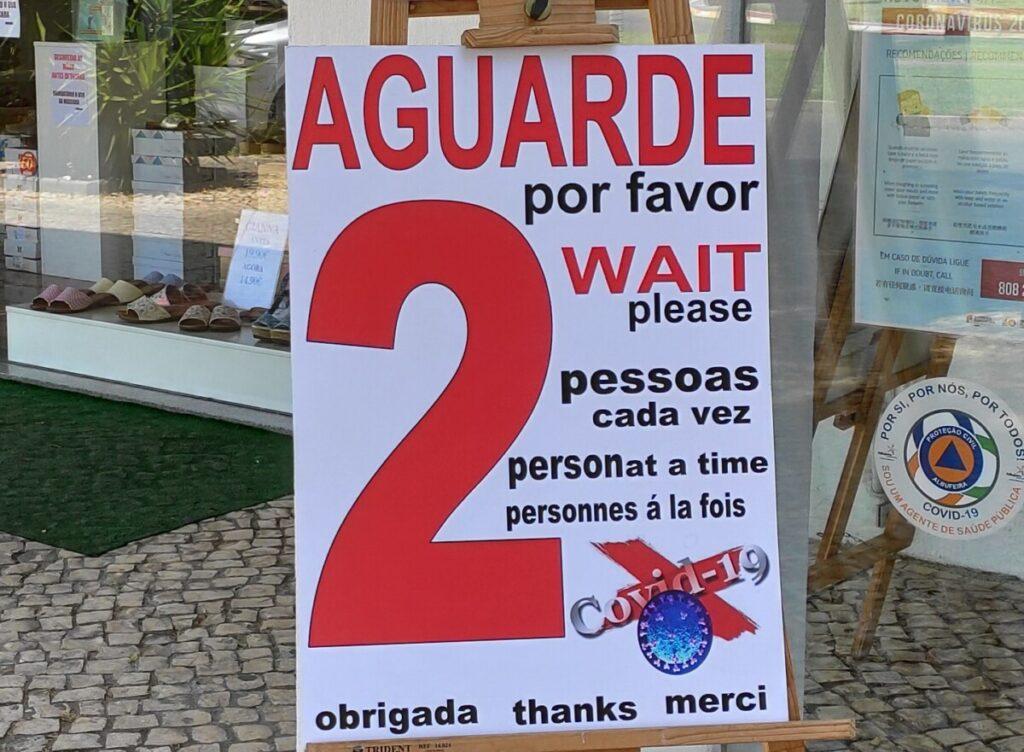 Waarschuwingsbord buiten een winkel in drie talen: er mogen slechts 2 personen tegelijk naar binnen.