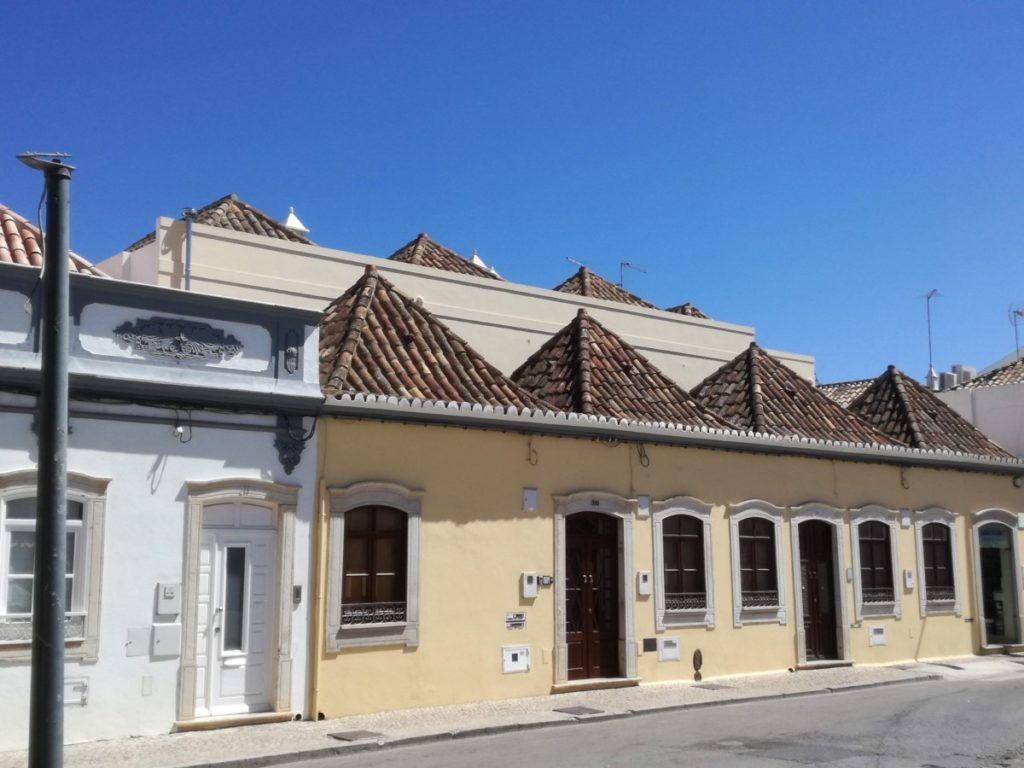 Een geel gebouwtje met vier telhados de tesouro,daken die typisch zijn voor Tavira.