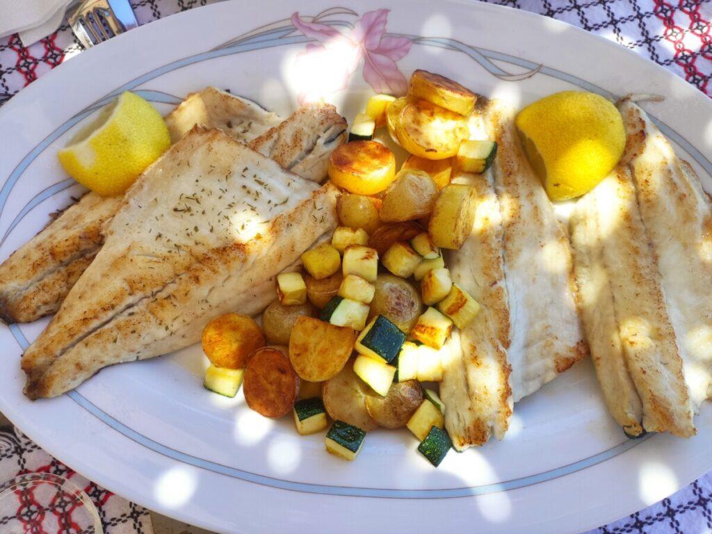 Schotel met vis, courgete en aardappels, in het zonlicht opgediend.