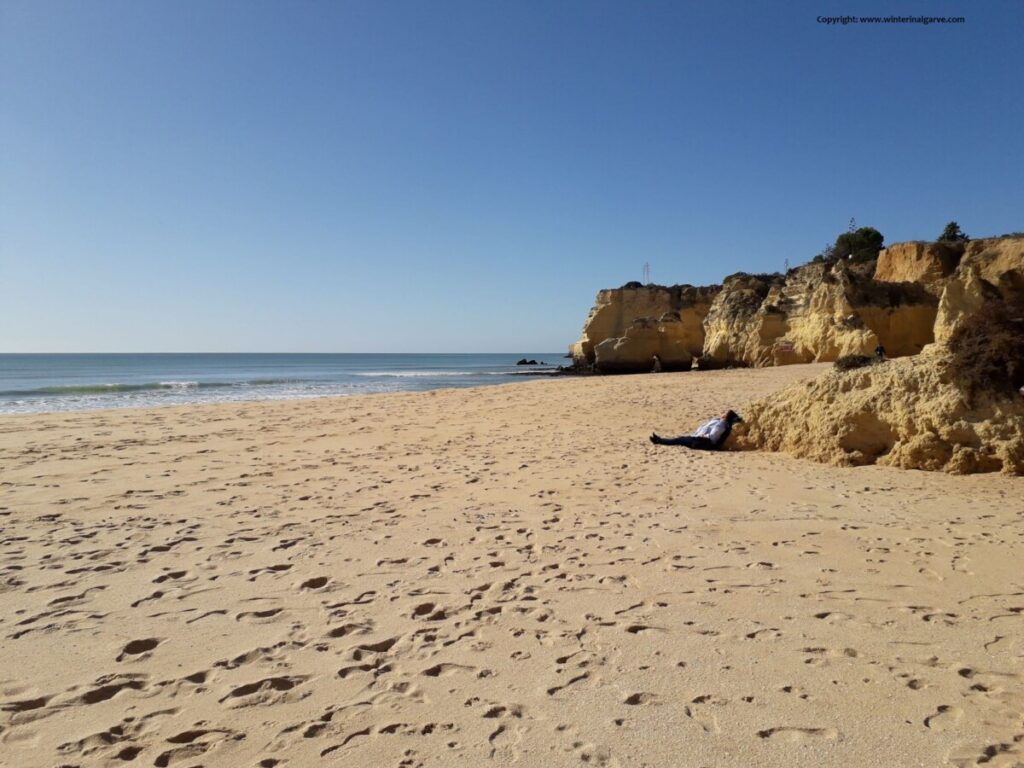 Vrouw met jas ligt op het strand met de zon op haar gezicht op een verlaten strand, in de Algarve in Portugal.
