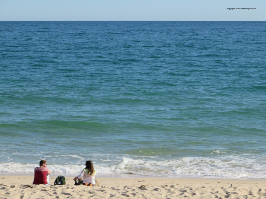 Verlaten strand met twee pratende dames op anderhalve meter afstand in de Algarve in Portugal