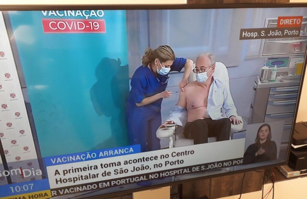 Foto van TV waarop de eerste coronavaccinatie in Portugal wordt uitgezonden.