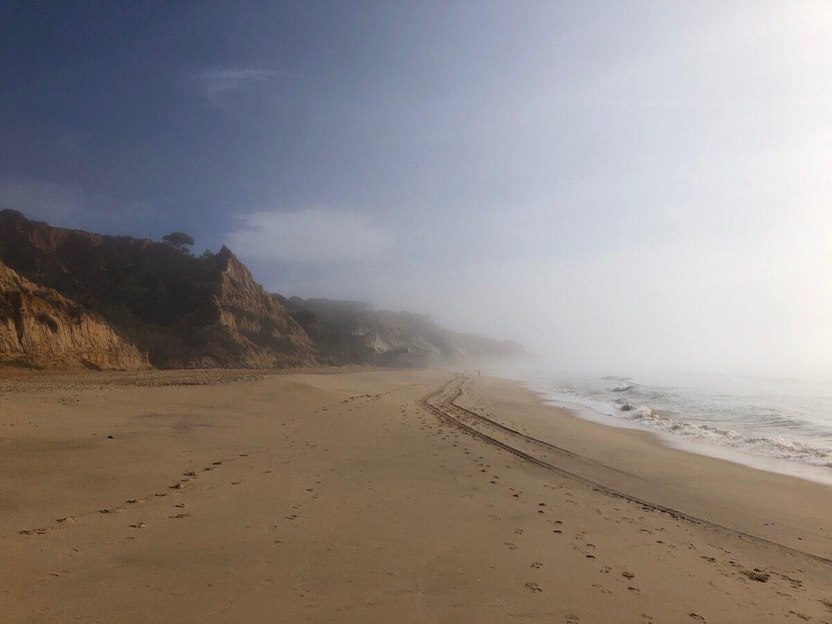 Amper wat te zien door de versluierende mistvlagen. Op het strand van Praia da Falésia.