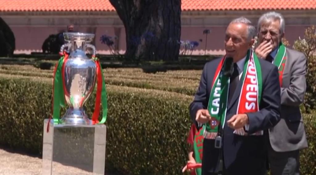 President Marcelo Rebelo de Sousa met Portugese voetbalsjaal om naast de beker met linten in de portugese kleuren groen en rood.