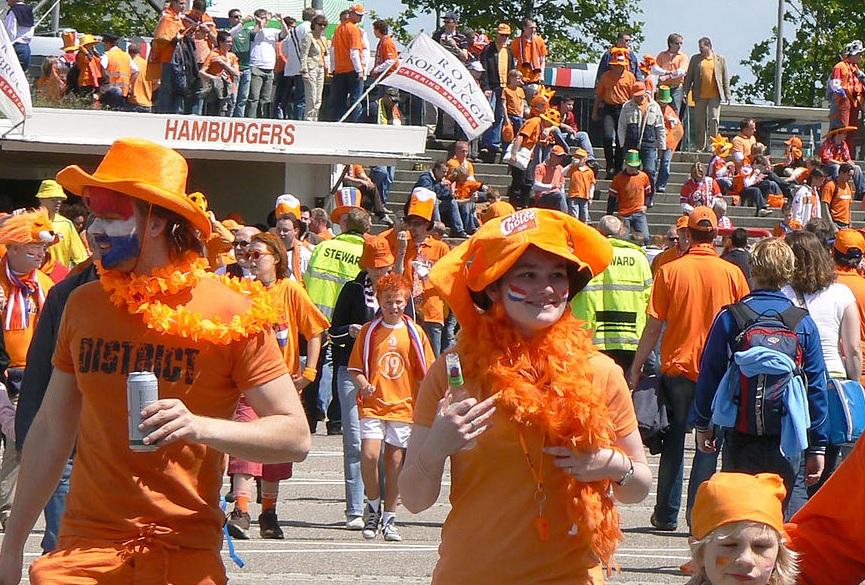 Tientallen mensen in allerlei oranje outfits gekleed.